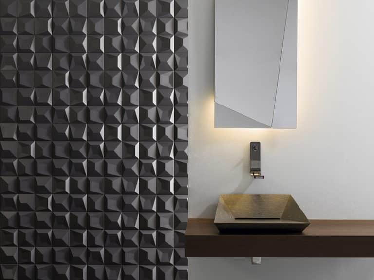 hnědé kamenné umyvadlo na dřevěné desce, černá geometrická mozaika a zrcadlo