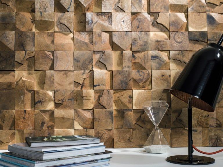 Dřevěná mozaika na zdi, knihy a lampička, přesýpací hodiny.