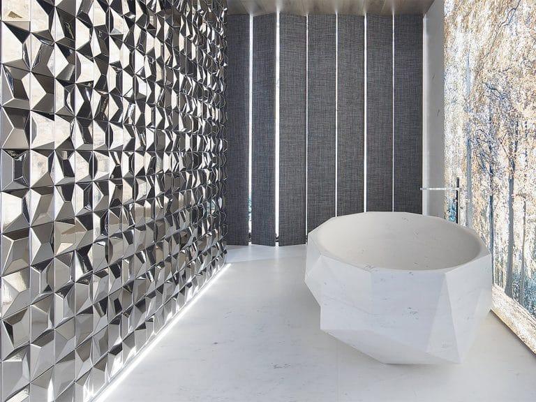 Koupelna s výhledem do lesa, stříbrná mozaika na zdi, bílá vana do prostoru.
