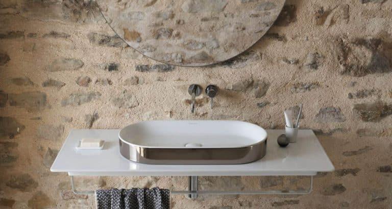 Ploché stříbrné umyvadlo na keramické desce s držákem na ručník
