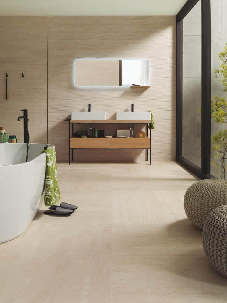 Koupelna v teplách tónech, béžová dlažba, vana do prostoru, béžový kamenný obklad