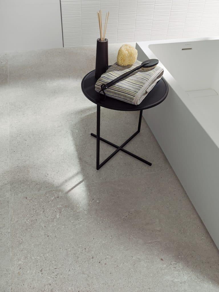 šedá dlažba v koupelně s imitací betonu, černý příruční stolek s ručníkem a difuzérem, vana z umělého kamene
