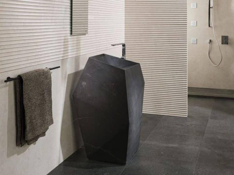Černé kamenné umyvadlo na postavení, černá dlažba, béžový obklad s reliéfem.
