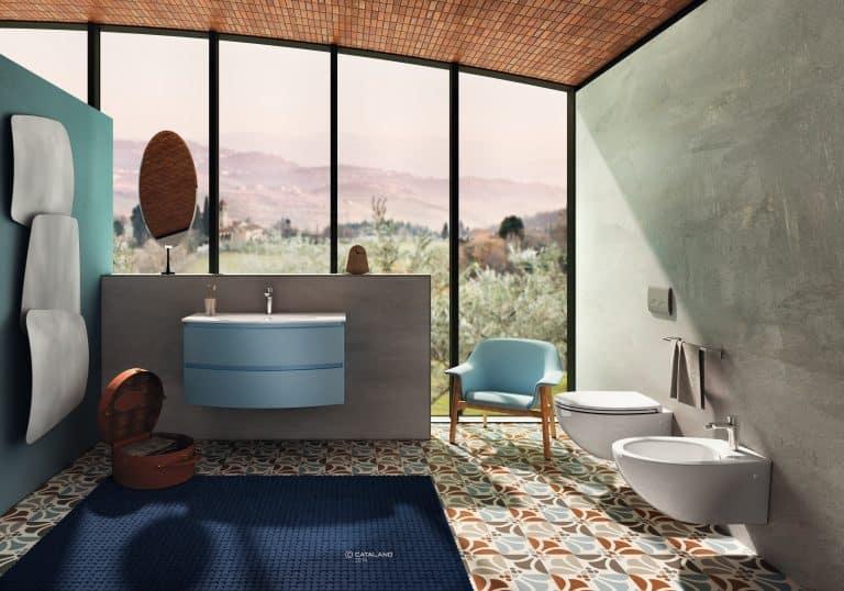 Koupelna s retro dlažbou, modrá skříňka pod umyvadlo se dvěma zásuvkami, modré křeslo, závěsné wc a bidet na zdi s betonovou stěrkou