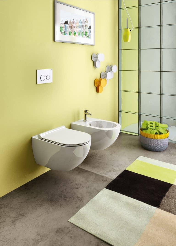Závěsné wc a bidet na žluté stěně, barevný koberec, koš na prádlo