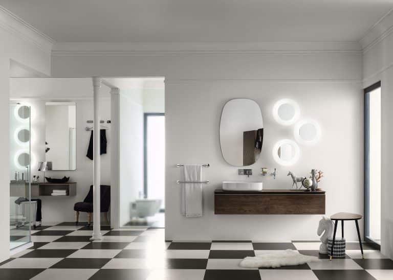koupelna s černobílou dlažbou, tmavě hnědý koupelnový nábytek, kulatá zrcadla, kožešina