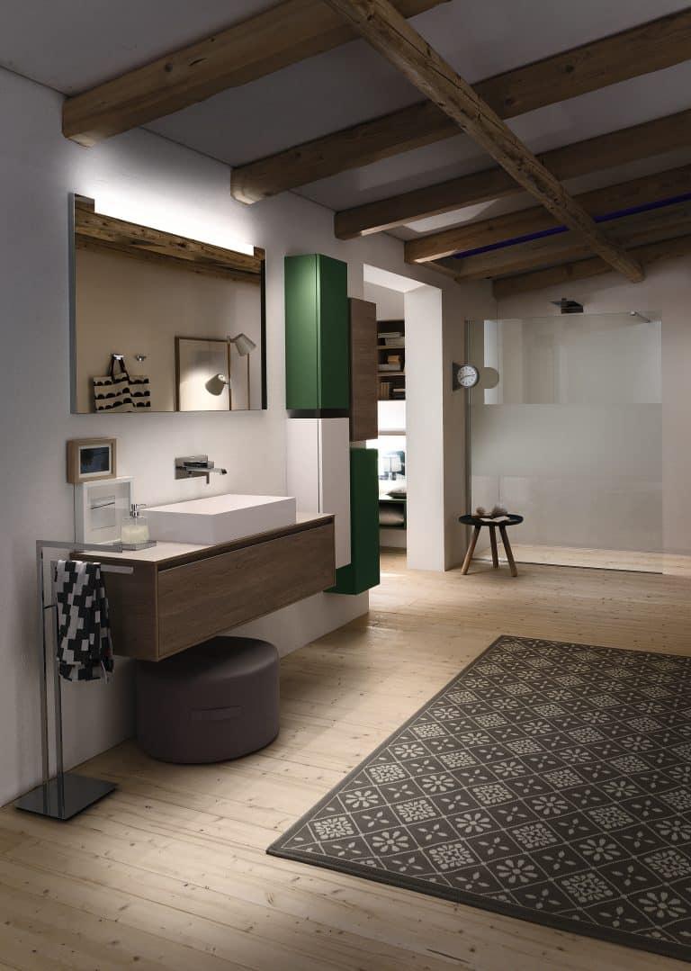 Koupelna v podkroví, trámy na stropě, barevné skříňky na zdi, dřevěná skříňka pod umyvadlo, černobílý koberec