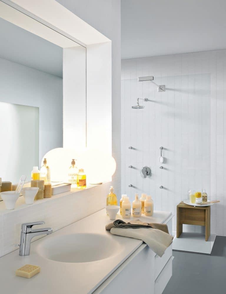Bílá koupelna s umyvadlem integrovaným do desky, chromová umyvadlová baterie, sprchová sestava s hlavovou sprchou, boční masážní trysky, sprchový kout typu walk-in