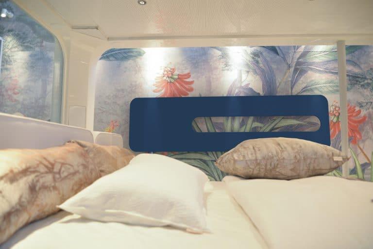 Ložnice s barevnou květinovou tapetou, modrý radiátor, postel s peřinami