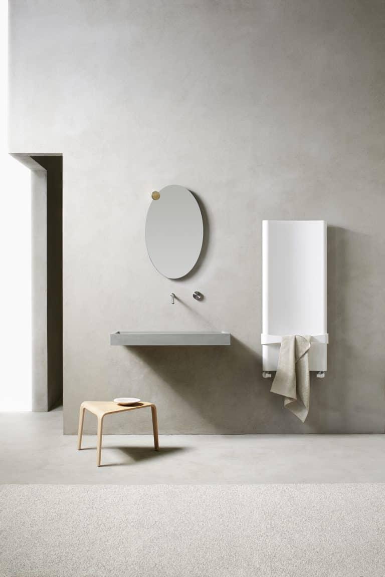 Betonová stěrka v koupelně, betonové umyvadlo, dřevěná stolička, bílý designový radiátor s držákem na ručník