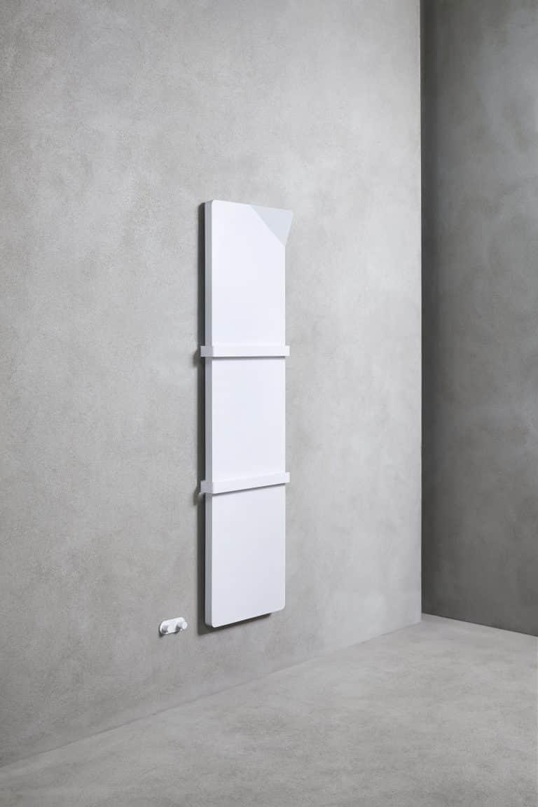Betonová stěrka na zdi a podlaze a bílý designový radiátor Book s držáky na ručník