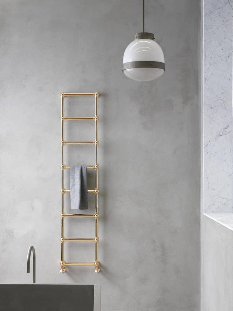 Betonová stěrka v koupelně, zlatý trubkový radiátor s ručníkem, bílý lustr