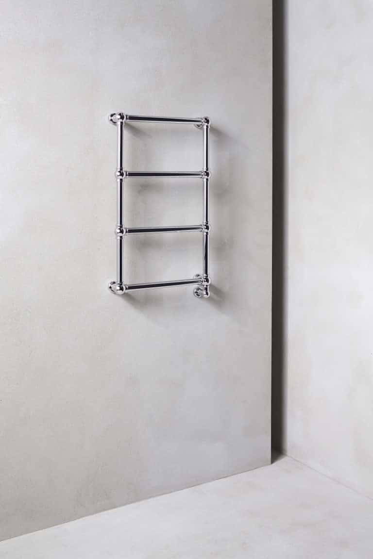 Betonová stěrka na zdi a stříbrný designový trubkový radiátor Caesar