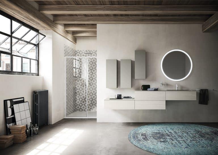 světle šedá koupelna se sprchovým koutem v nice, dřevěnou skříňkou pod umyvadlo, kulaté zrcadlo, kulatý zelený koberec