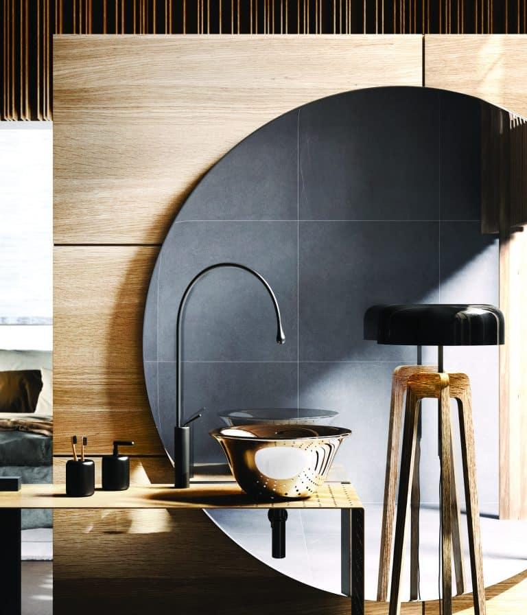 Zlaté umyvadlo na desce, černá baterie, černé doplňky, velké kruhové zrcadlo, černá lampa