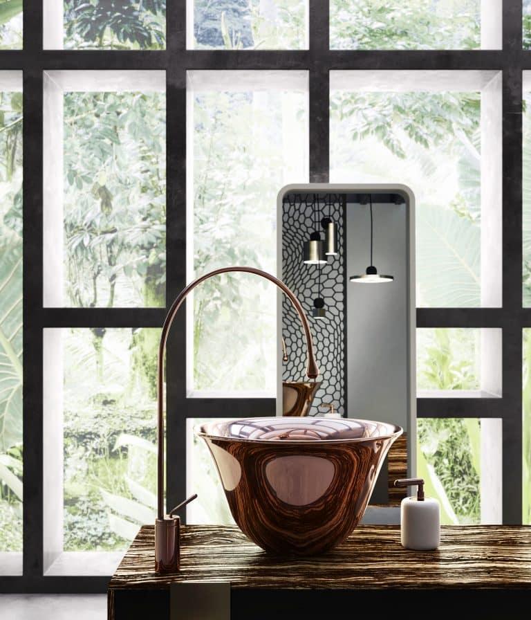 Měděná lesklá baterie a umyvadlo na desce, zlatý dávkovač na mýdlo, bílé zrcadlo, výhled do zahrady