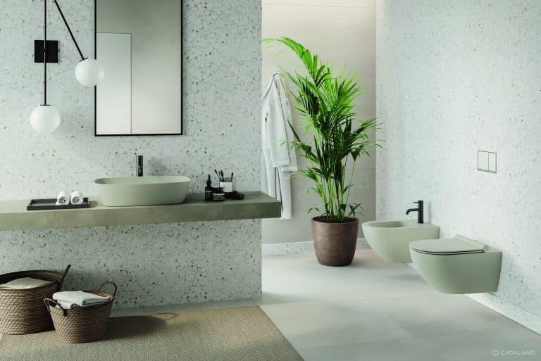 Šedé matné umyvadlo položené na desce, šedé wc a bidet zavěšené na zdi, koše na prádlo, velká květina v koupelně