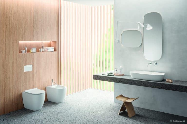 Bílá matná sanitární keramika, wc a bidet na postavení, umyvadlo na kamenné desce, dřevěná stolička
