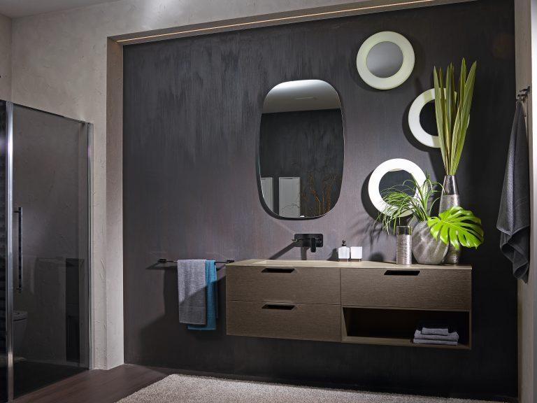 tmavě šedá koupelna s hnědým dřevěným nábytkem, kulatá zrcadla, šedá stěrka na zdi
