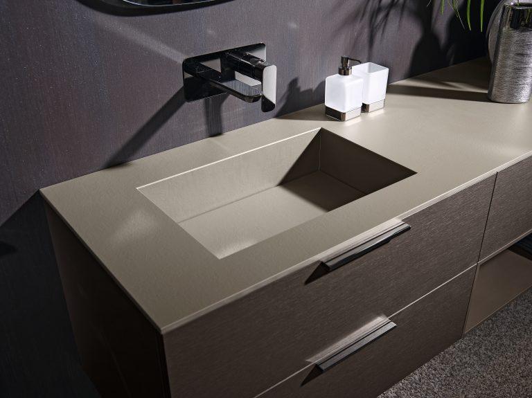 Šedé umyvadlo zapuštěné do desky na dřevěné skříňce ze dvěma zásuvkami