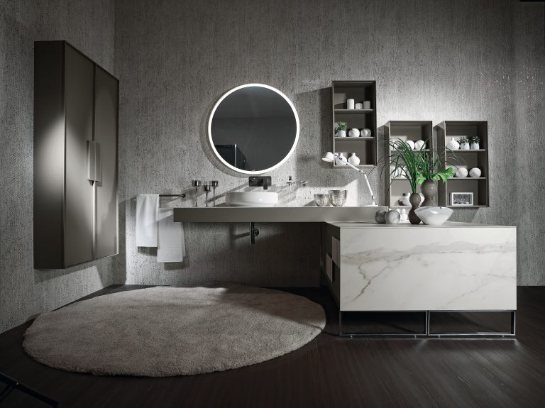 světle šedý nábytek v koupelně, kulaté zrcadlo, malé umyvadlo na desce,kulatý koberec