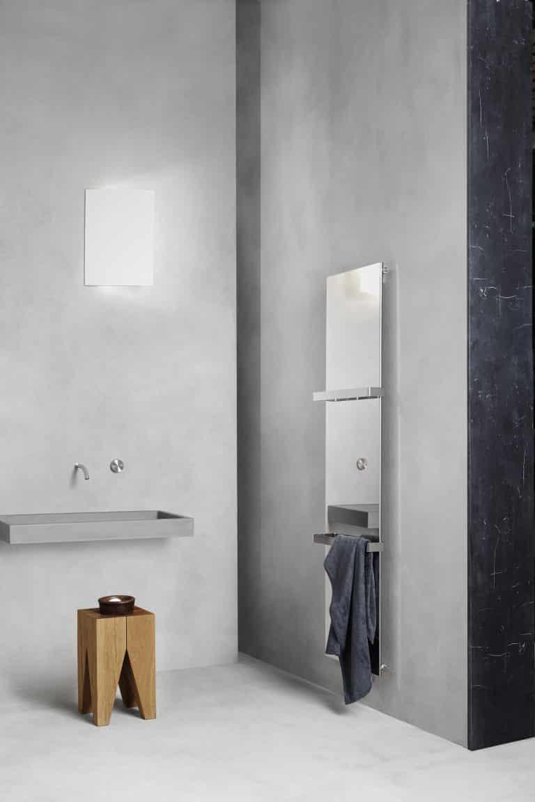 Betonová koupelna, betonové umyvadlo, dřevěná stolička a designový lesklý chromový radiátor s držákem na ručník