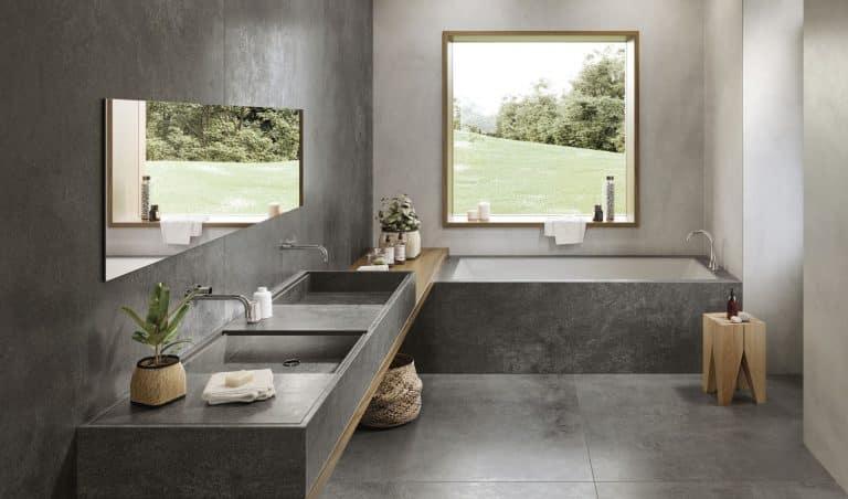 Tmavá koupelna s černou dlažbou a obkladem imitujícím kámen a beton, dřevěná deska pod umyvadlem, černé umyvadlo, chromové baterie