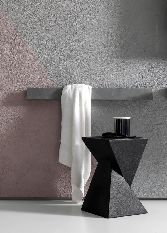 šedý držák na ručník na zeď, černá stolička do koupelny