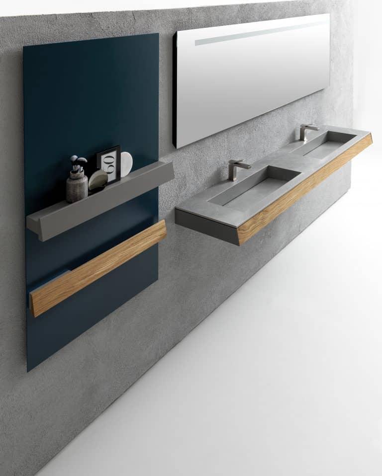 Šedá koupelna, dřevěná deska pod umyvadlo, šedá kamenné dvojumyvadlo s bateriemi, zelený nábytek s policemi na kosmetiku