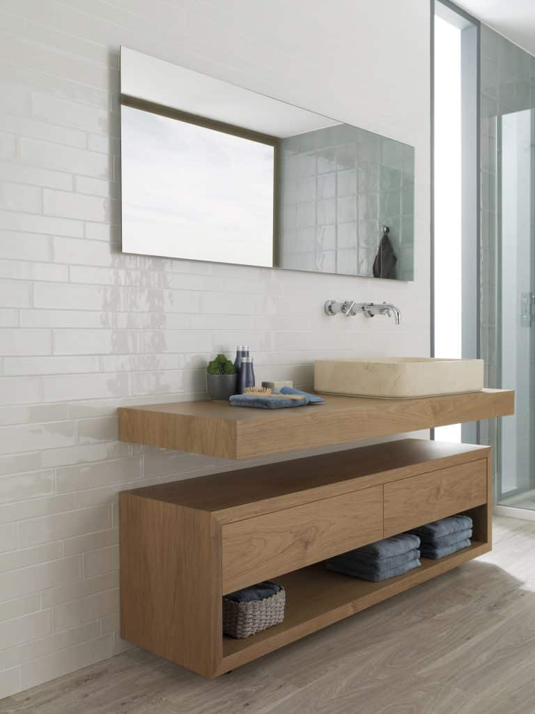 Bílá koupelna s lesklým obkladem, kamenným umyvadlem a dřevěnou skříňkou