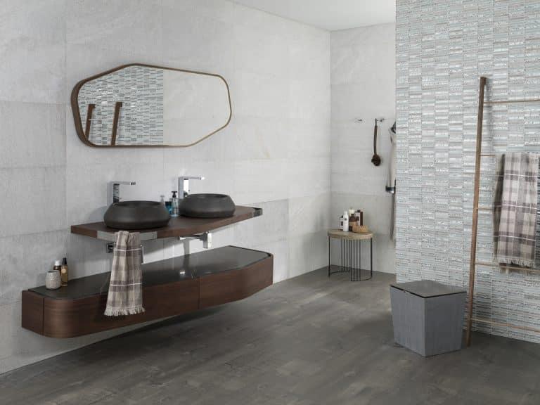 Šedá koupelna se skleněnou mozaikou, dřevěným nábytkem a černými umyvadly