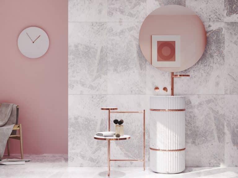 Růžová koupelna s obkladem z mramoru, kamenným umyvadlem a zlatou baterií