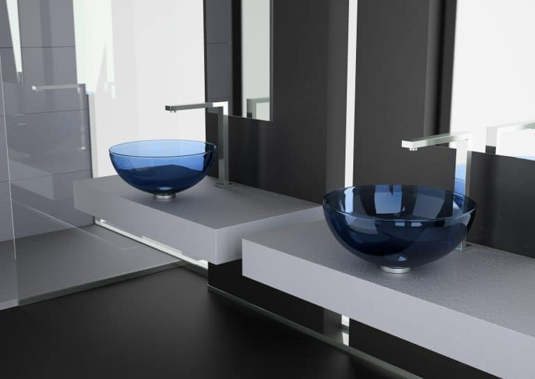Modrá skleněná umyvadla na desce, chromové baterie, černá podlaha