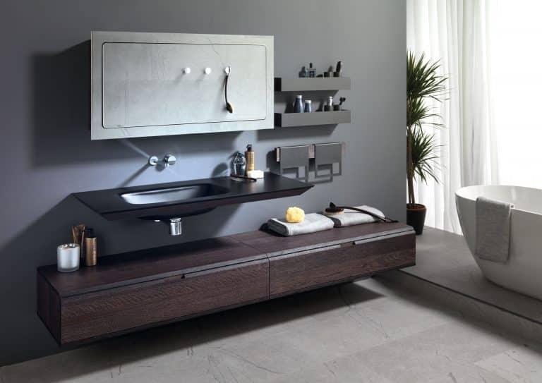 černá koupelna, černé umyvadlo z umělého kamene, dřevěný nábytek, velké zrcadlo, černé police, vana do prostoru, palma v koupelně