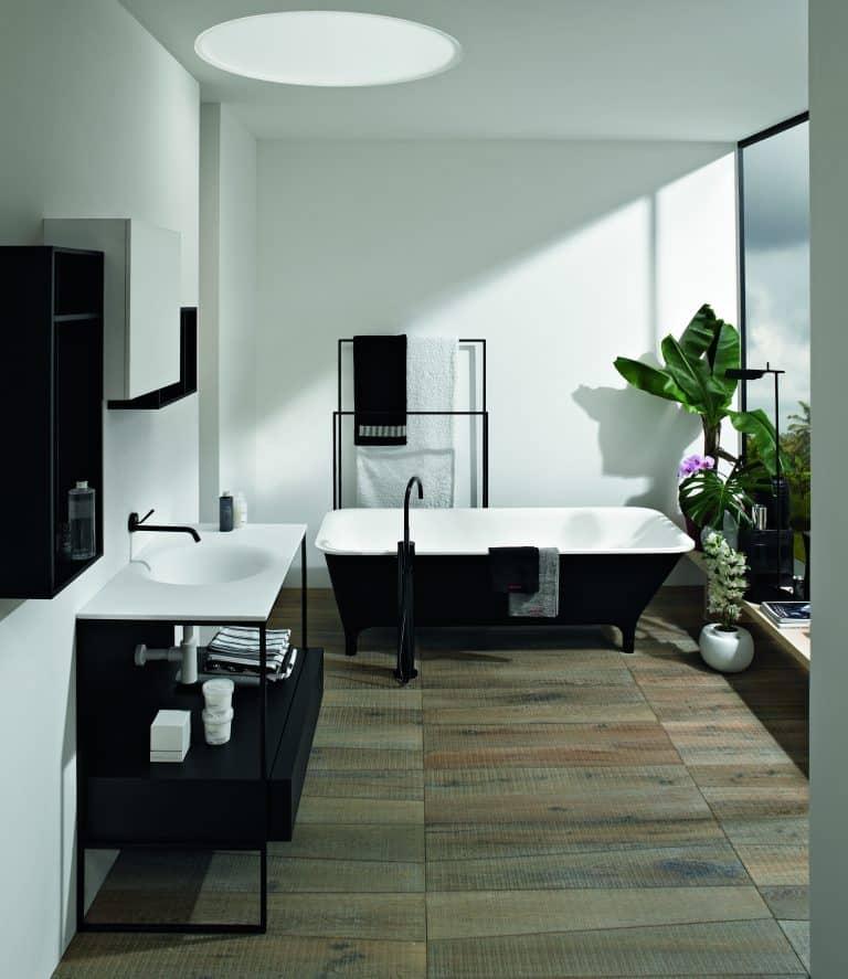 bílá koupelna s černou vanou do prostoru, černá vanová baterie, kytky, černá konzole pod umyvadlo a černé baterie