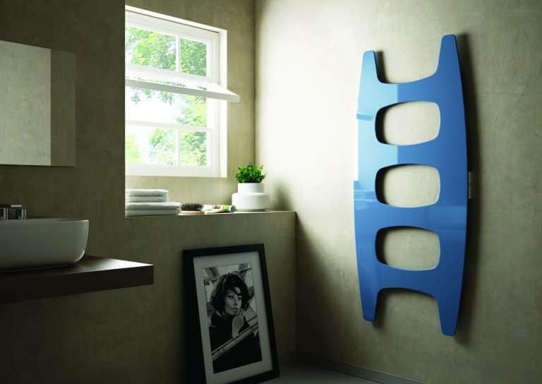 Koupelna s betonovou stěrkou, fotografie na zdi, modrý designový radiátor