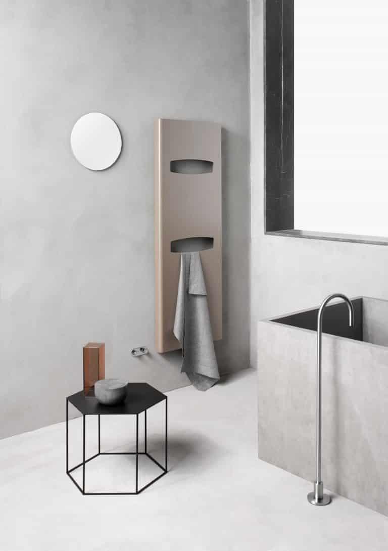 Koupelna s betonovou stěrkou, betonová vana, černý kovový odkládací stolek, designový radiátor