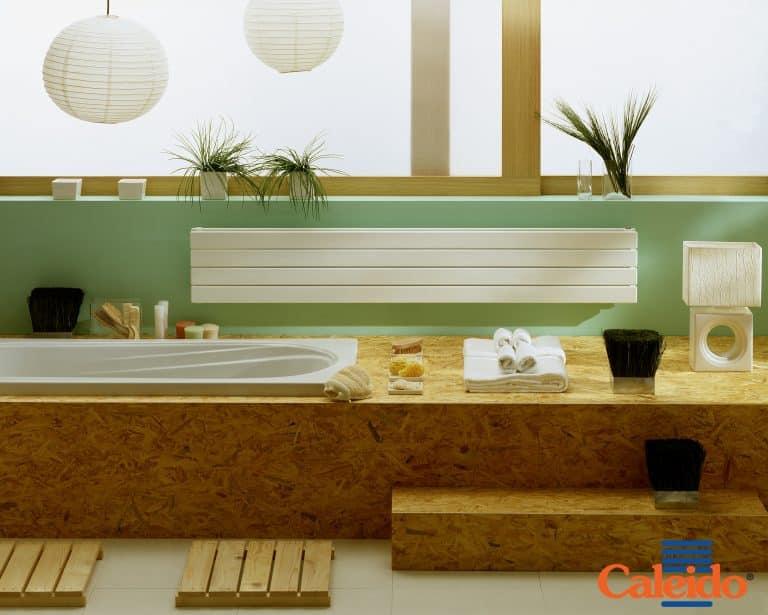 Dřevěná koupelna se zapuštěnou vanou, schody do vany, bílý radiátor, květiny v koupelně