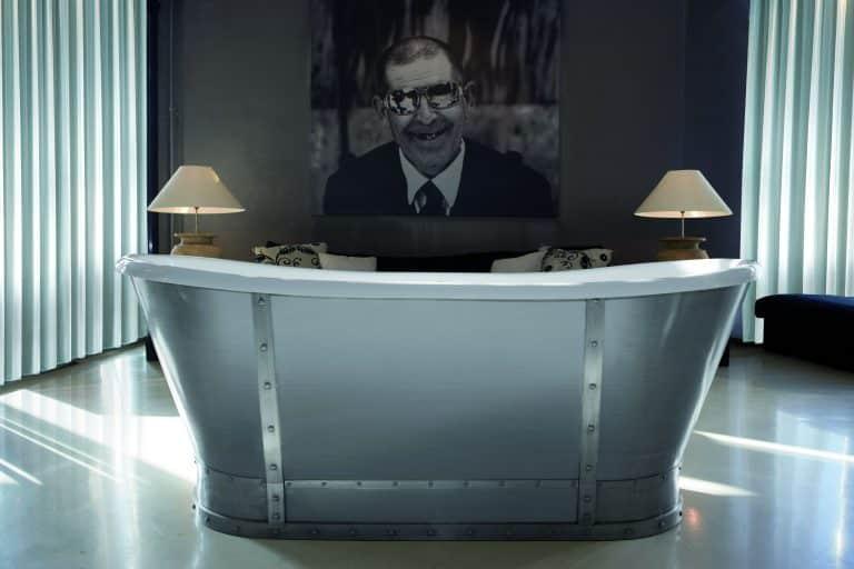 Kovová vana v koupelně s obrazem muže v brýlích