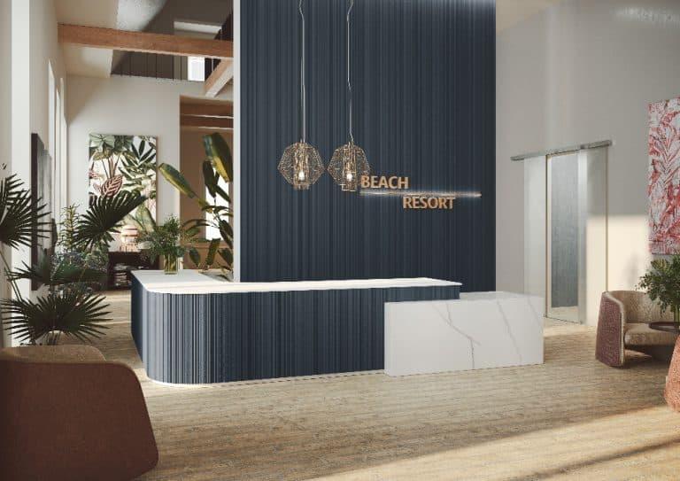 Recepce hotelu s černýnm obkladem na zdi a recepčním pultu, palmy v květináči, zlaté lustry