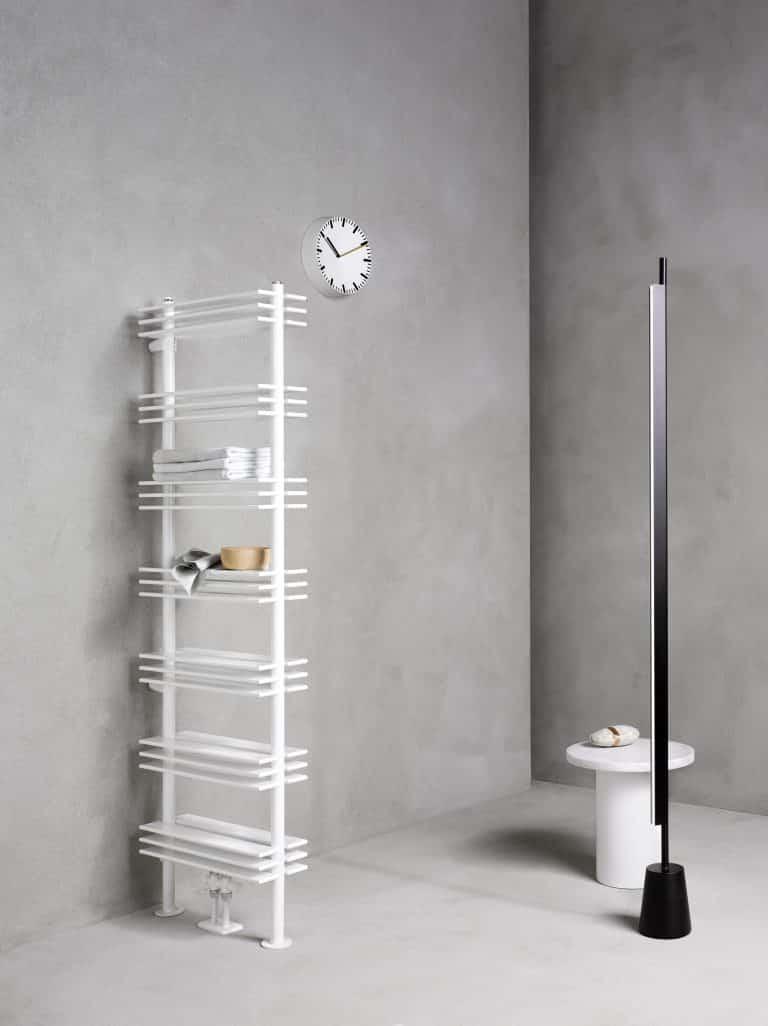 Radiátor do prostoru s odkládacími poličkami, bílý stolek, hodiny