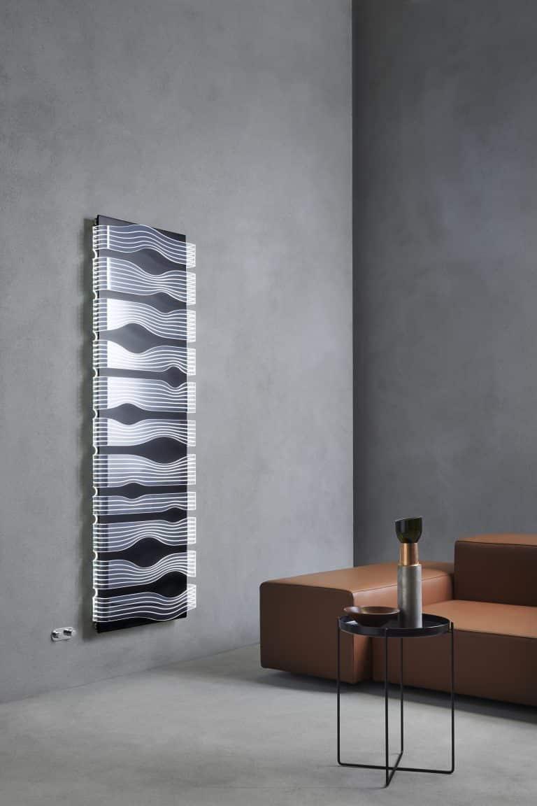 Svítící designový radiátor v obýváku s hnědou koženou sedačkou a černým kovovým stolkem