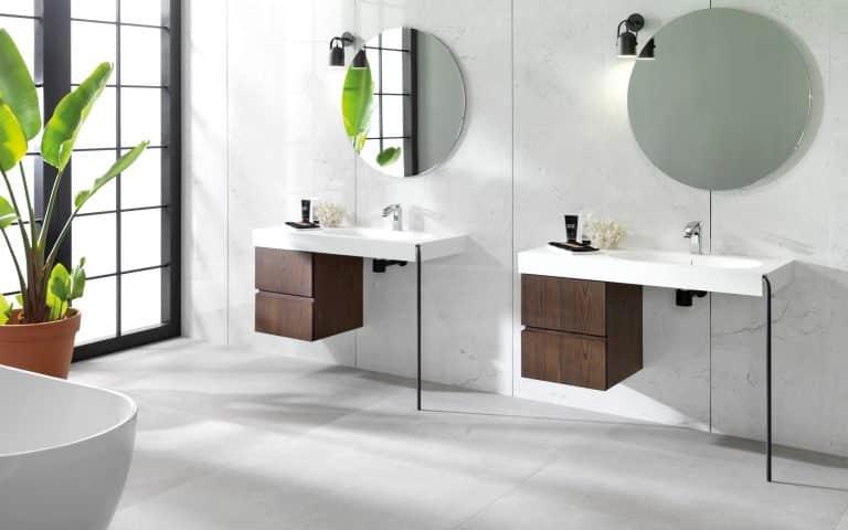 dřevěné skříňky pod umyvadlo, kulaté zrcadlo, kytka v koupelně, vana do prostoru