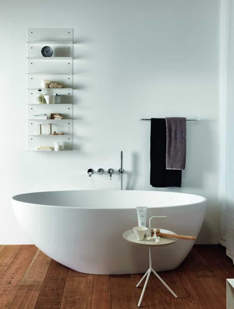 koupelna s dřevěnou podlahou, vana do prostoru z umělého kamene, odkládací stolek