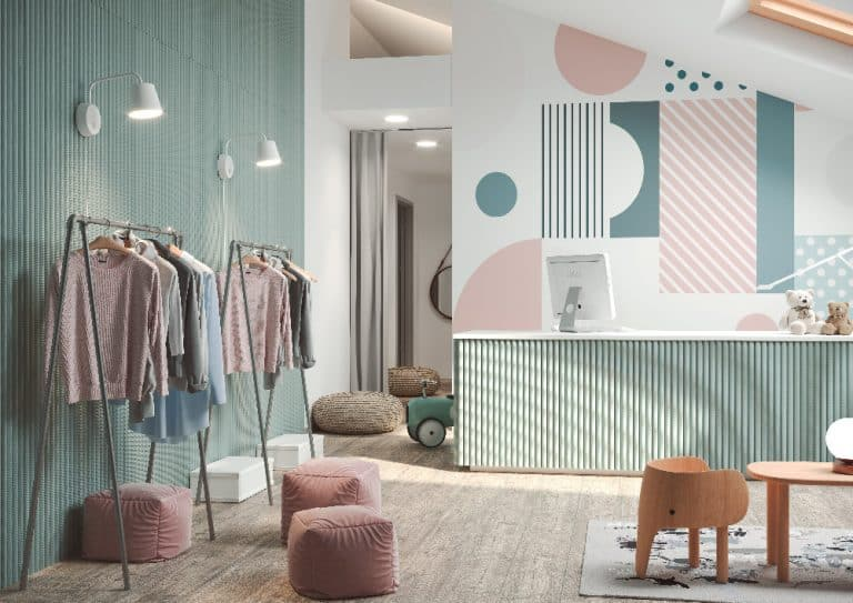 obchod s oblečením, stěny z umělého kamene, pastelové barvy, věšáky s oblečením, dřevěná židlička a stůl