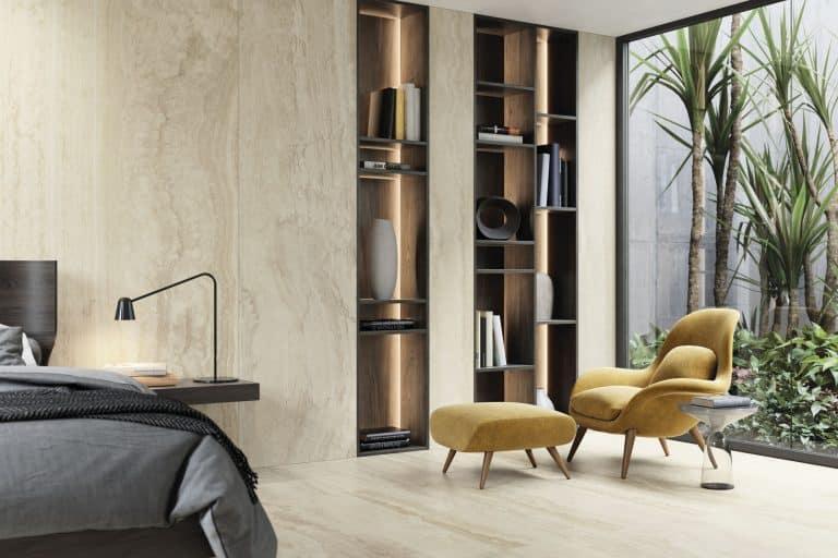 Ložnice s velkoformátovým obkladem imitujícím béžový mramor, žluté křeslo a podnožník, poličky s dekoracemi a knihami, postel, palmy za oknem