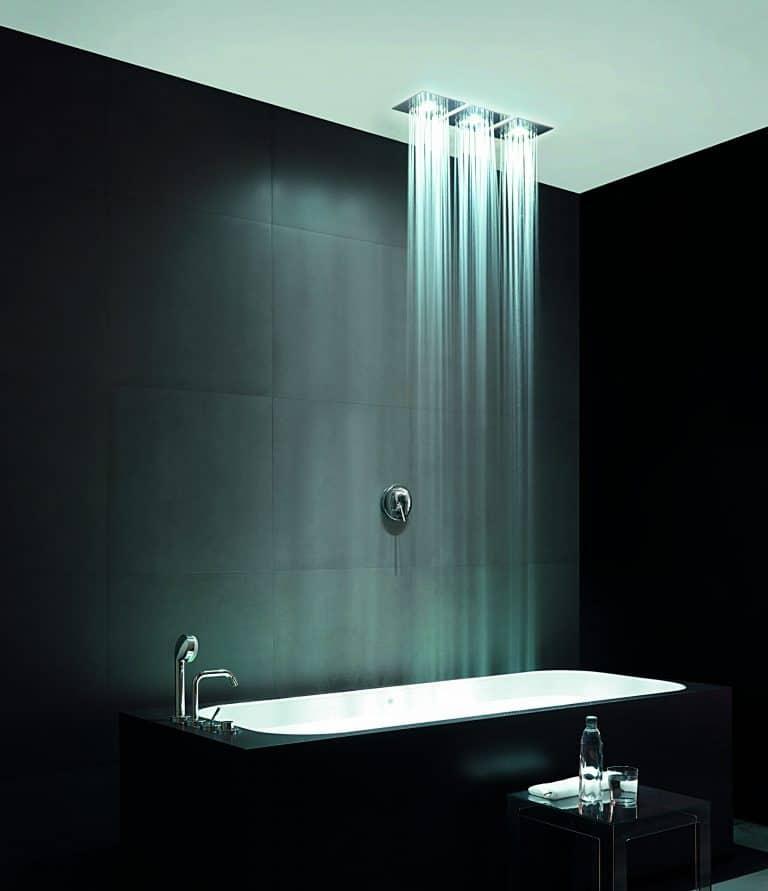 Hlavové sprchy s osvětlením a tropickým deštěm zabudované v podhledu nad černou vanou, černý obklad na zdi, černý příruční stolek