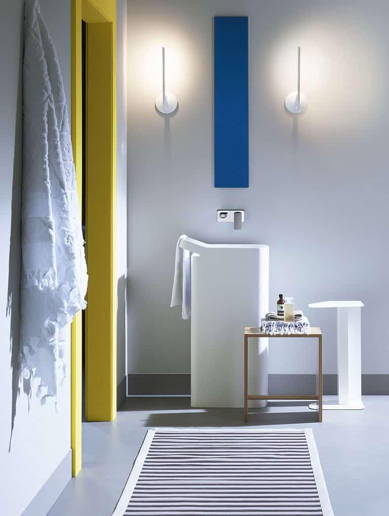 šedá koupelna, běhoun, umyvadlo na postavení z umělého kamene, žluté zárubně