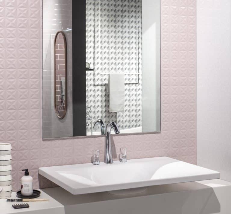 Růžová koupelna s hranatým zrcadlem, umyvadlem na desce a tříotvorovou baterií se skleněnými madly