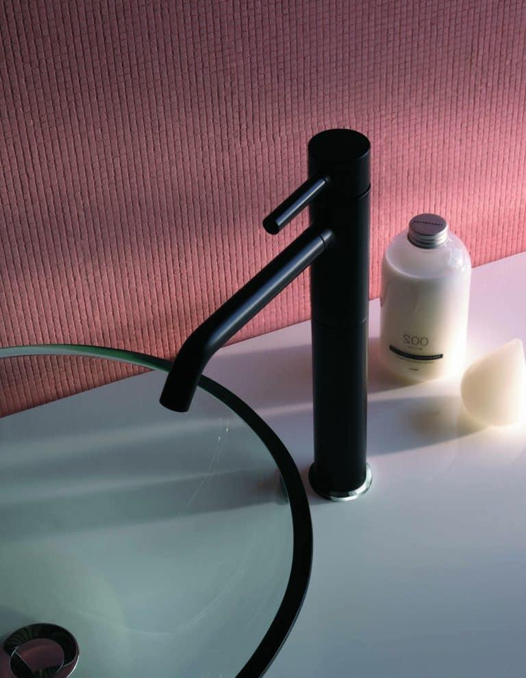 Matná černá umyvadlová baterie na desce se skleněným umyvadlem, růžový obklad na zdi